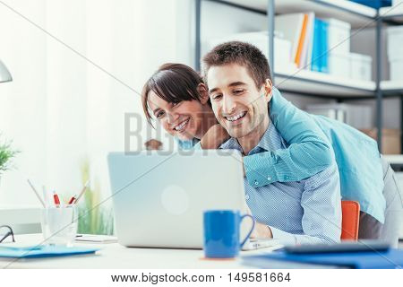 Happy Couple Using A Laptop At Home