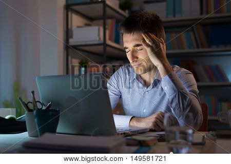 Businessman in the office working late at night and having a bad headache overwork and stress concept