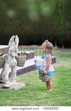 Little Cute Girl Looking At Sculpture Of Burro In Summer Garden,