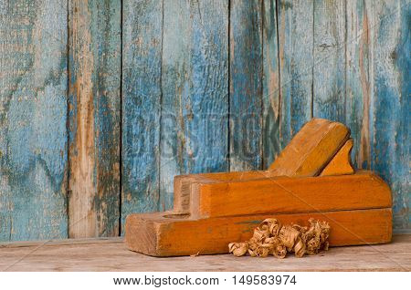 Old wooden plane and chips on a background of the old wall
