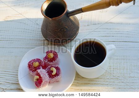 Coffee Mug Turkish delight with nuts and copper Cezve on a light wooden table in the sunlight