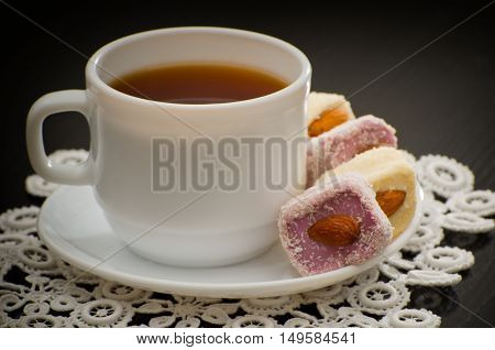 Mug of tea and Turkish delight with nuts on a plate close-up black background