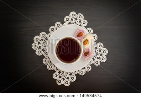 Top view of a cup of coffee and Turkish delight with almonds on a saucer lace doily