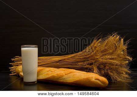 Glass of milk and fresh loaf and a sheaf on a black background