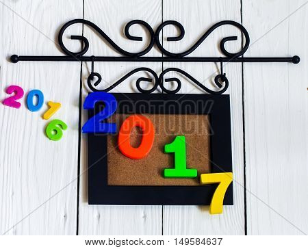 Expiring 2016.New year 2017 the figures in the picture frame on white wooden background.