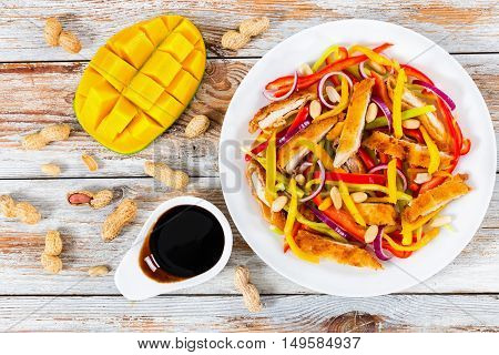 bread crumbed chicken meat mango peanuts bell pepper red onion salad on white dish with half of mango cutting in cubes balsamic vinegar dressing on white peeling paint boards view from above