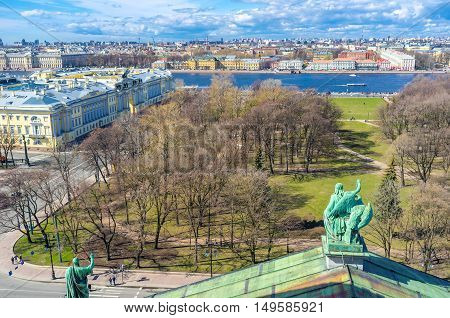 The bronze sculpture of St John the Apostle with Eagle on the St Isaac's Cathedral's roof overlooks the Alexander Garden and Neva river with Vasilyevsky Island on the background St Petersburg Russia.
