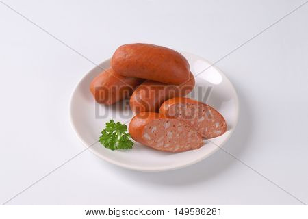whole and sliced short sausages on white plate