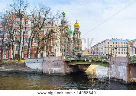 SAINT PETERSBURG RUSSIA - APRIL 25 2015: The old Malokonushenny bridge across the Moyka River leads to the Church of the Savior on Spilled Blood on April 25 in Saint Petersburg.