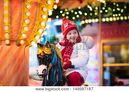 Happy little girl in warm jacket and red knitted Nordic hat and scarf riding carousel horse during family trip to traditional German Christmas market. Kids at Xmas outdoor fair on snowy winter day.