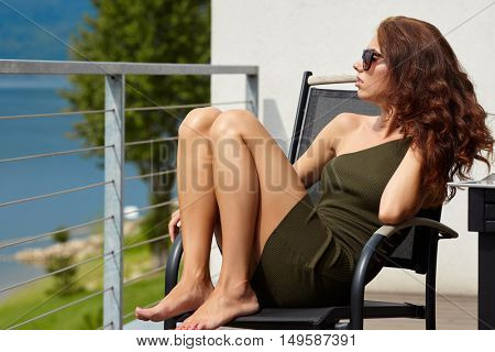 Dreamer woman pensive sitting in a house terrace with the beach in the background
