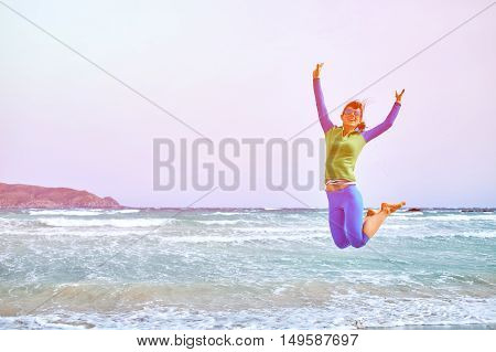beautiful athletic woman jumping on the beach along the sea front