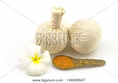Spa herbal compressing ball white frangipani flowers (Plumeria spp Apocynaceae Pagoda tree Temple tree) and turmeric powder in wooden spoon on white background