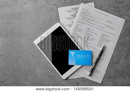 Medical service concept. Visiting card and tablet on grey background