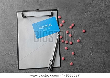 Medical service concept. Visiting card, clipboard and drugs on grey background