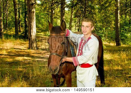 image of a young Ukrainian with a horse in the forest
