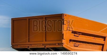 Fragment of a truck, truck, tip truck, tip lorry, orange truck on a blue sky background