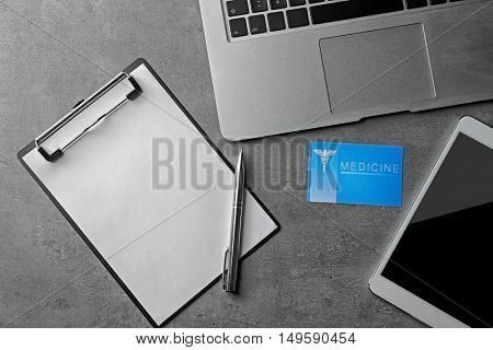 Medical service concept. Visiting card, clipboard, laptop and tablet on grey background