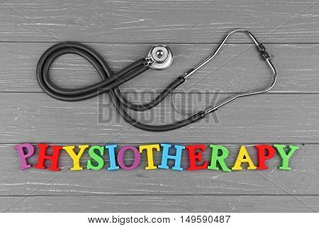 Medical concept. Stethoscope and colourful word Physiotherapy on grey wooden background