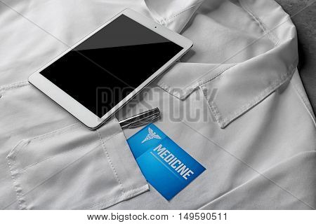 Medical service concept. Visiting card and tablet on doctor uniform