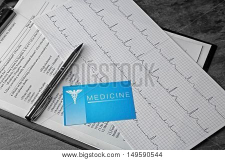 Medical concept. Medical history, business card an ECG chart on grey background