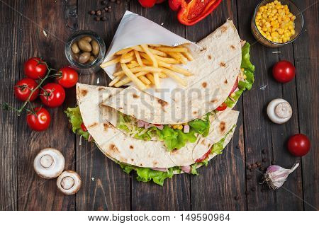 Sandwiches twisted roll Tortilla two pieces and french fries on a wooden background.