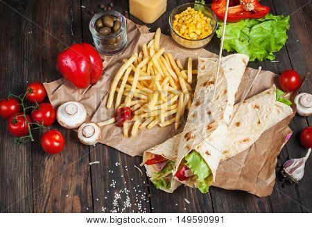 Sandwiches twisted roll Tortilla two pieces and french fries on a wooden background