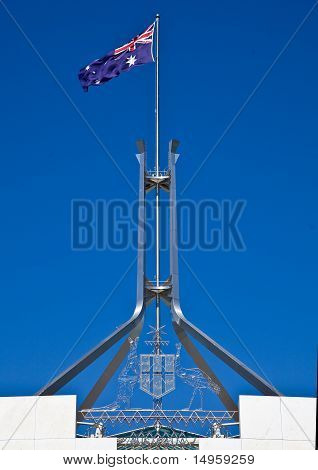 Flag flies on giant flagpole over Parliament House in Canberra