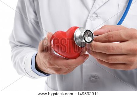 Male doctor holding red heart and stethoscope, closeup
