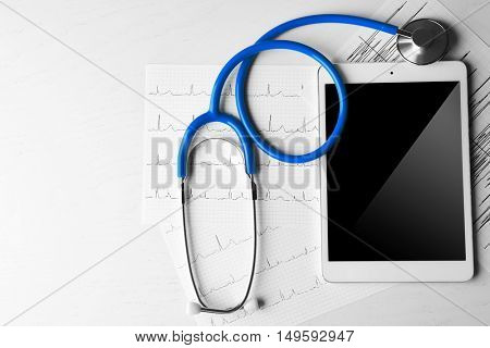 Stethoscope, tablet and cardiogram on white wooden background