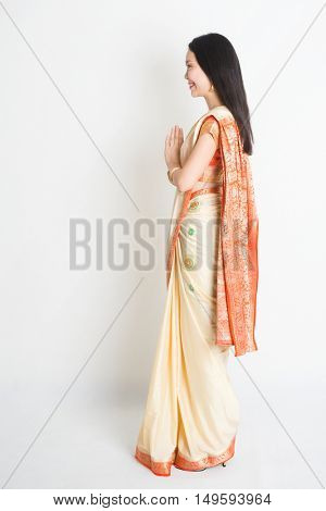 Full length side view mixed race Indian Chinese female with sari dress in greeting gesture, standing on plain background.