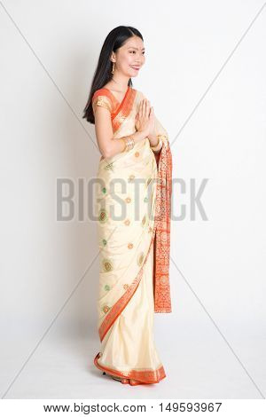 Full length mixed race Indian Chinese woman with sari dress in greeting gesture, standing on plain background.