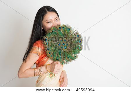 Portrait of young mixed race Indian Chinese female in traditional sari dress, holding peacock feathers fan covering face, on plain background.