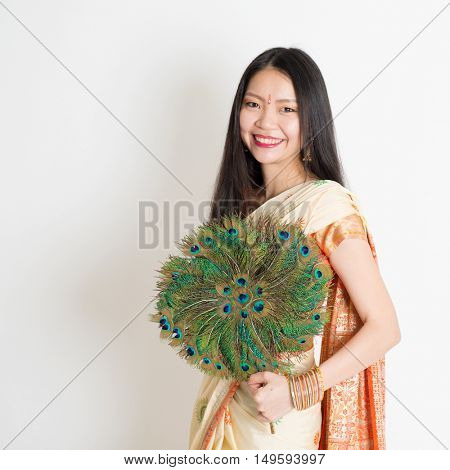 Portrait of young mixed race Indian Chinese female in traditional sari dress, holding peacock feathers fan and looking at camera, on plain background.