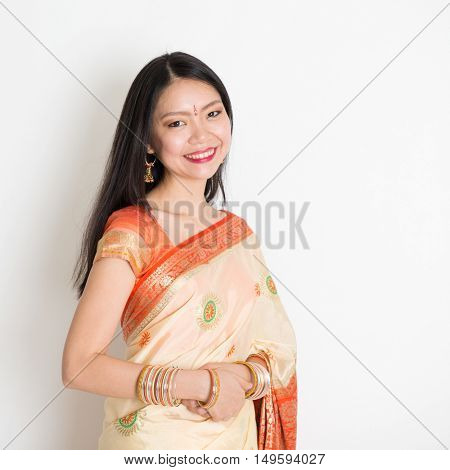 Portrait of mixed race Indian Chinese girl with traditional sari dress smiling, standing on plain background.