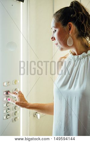 Side view of adult woman in white blouse with ponytail pushing button with finger inside elevator