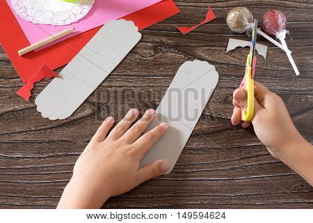 The Child Create A Greeting Packaging For Candy Santa Claus On Paper, Cut In Parts Paper. Children's