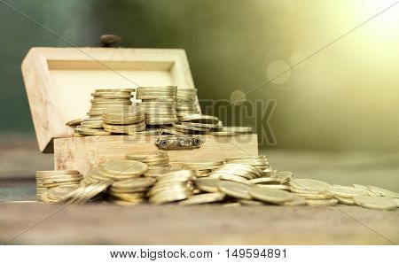 Golden money coins in a wooden box - fortune lottery win concept