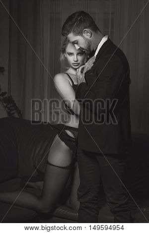 Sexy blonde woman cuddle up to rich macho man at night black and white sensuality