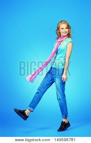 Full length portrait of a pretty smiling young woman in casual clothes posing in motion.