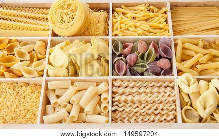 Assortment of different pasta in wooden crate as a background