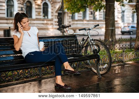 Beautiful casual girl talking on the mobile phone while sitting on the bench with cup of coffee
