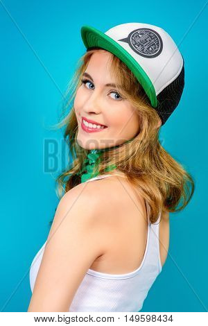 Cheerful smiling young woman in casual t-shirt and baseball cap. Beauty, youth  style. Healthy white teeth. Studio shot.