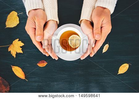 Couple Man and Woman in Love hugging holding hands with hot tea lemon cup on wooden table with autumn leaves Romantic relationship feelings concept top view trendy style