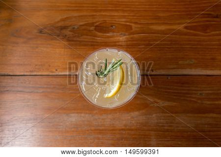 Lemonade in plastic cup on wooden table. Top view