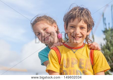 two happy kids - boy and girl - outdoor portrait