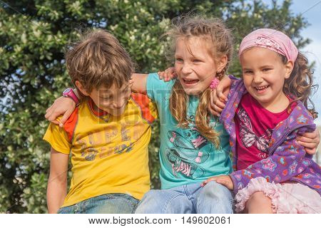 three happy kids - boy and girls - outdoor portrait