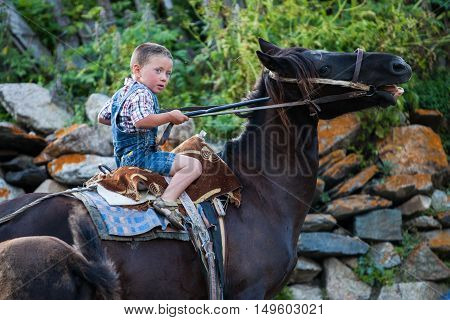 Ushguli Georgia - August 15 2016: Color image of a young boy riding a horse in the Caucasian village of Ushguli Georgia.