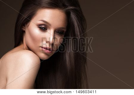 Beautiful brunette girl with a perfectly smooth hair and classic make-up. Beauty face. Picture taken in the studio.