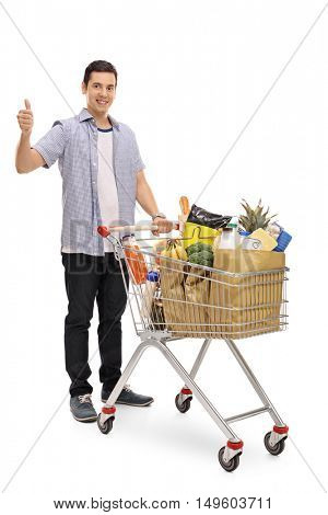Full length portrait of a guy posing with a shopping cart and giving a thumb up isolated on white background